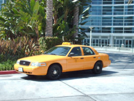 A taxi cab leaves after a pickup.