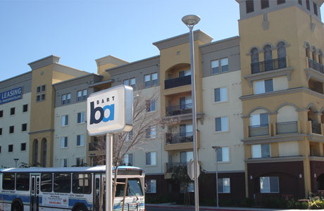 A city bus parked on the street between a BART station sign and a new condo development.
